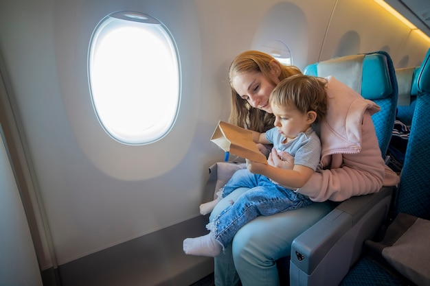 Young beautiful mother and little cute toddler sit in an airplane chair open a cardboard bag