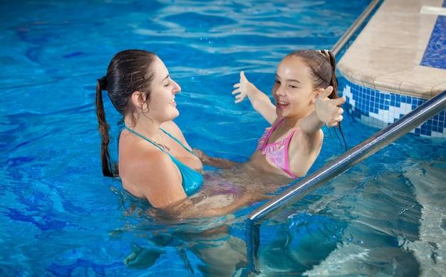 スイミング プールで娘と遊ぶ若い美しい母親