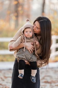 Молодая красивая мать играет с дочерью в осеннем парке в солнечный день