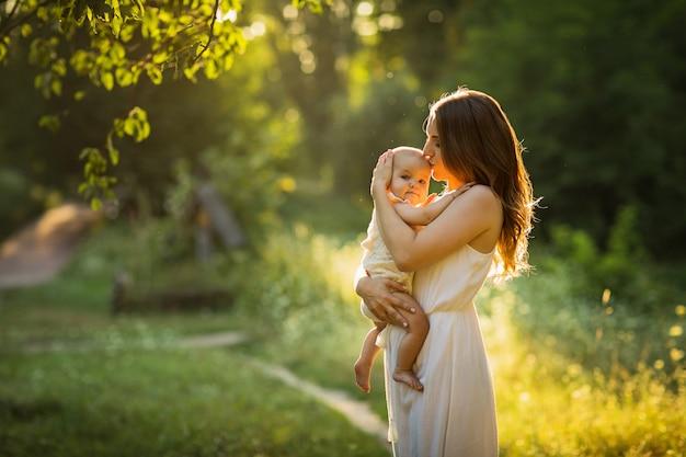 若い美しい母親は、屋外で子供と遊んでいます。