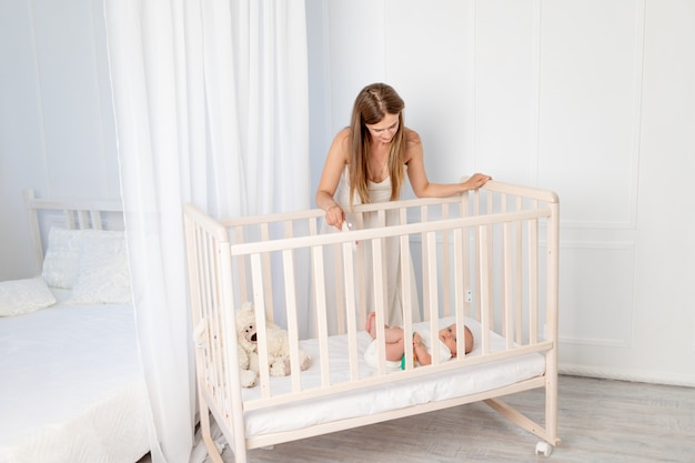 A young beautiful mother puts a 6-month-old baby in a crib, leaning over it in the nursery, mother's day, baby's morning, place for text