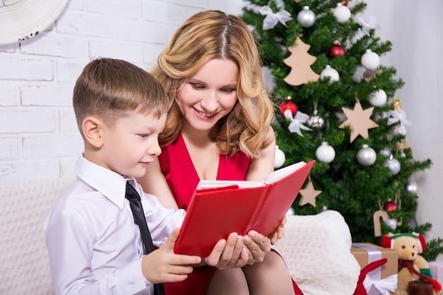 크리스마스 트리 앞에서 그의 아들에게 책을 읽는 젊은 아름다운 어머니
