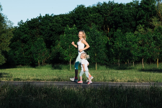 Young beautiful mother running with little daughter in the park