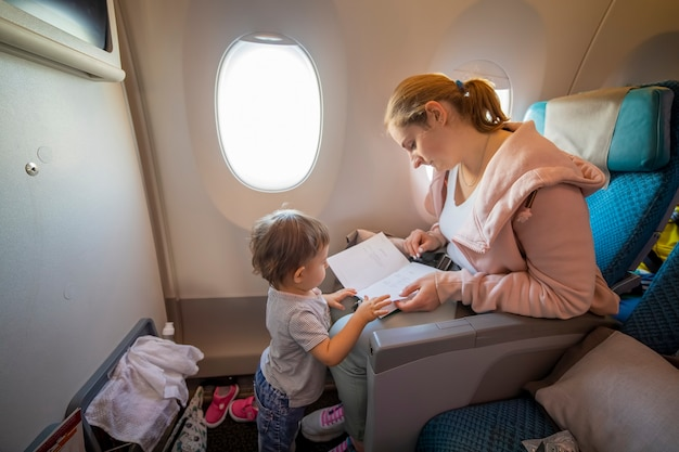 A young beautiful mother sits in an airplane chair and shows her little cute baby a book