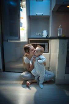 늦은 밤 부엌 바닥에 아기 아들과 함께 앉아 있는 아름다운 젊은 어머니