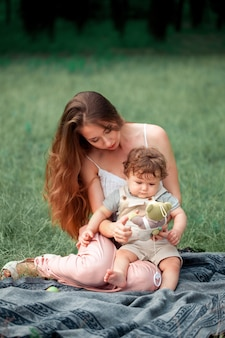 Young beautiful mother sitting with her little son against green grass. happy woman with her baby boy on a summer sunny day. family walking on the meadow.