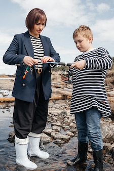 Young, beautiful mother and son have fun fishing on the lake. mom and son in striped vests on the river bank with a fishing rod.