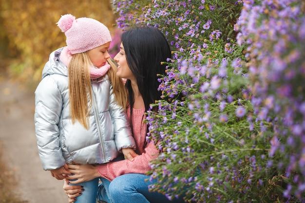 秋の時間に彼女の小さなかわいい娘と一緒に時間を過ごす若い美しい母親