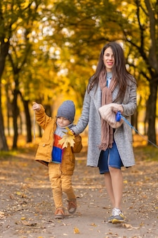 Молодая красивая мама проводит время на прогулке с любимым сыном в осеннем парке
