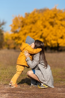 Молодая красивая мама проводит время на прогулке с любимым сыном в осеннем парке.