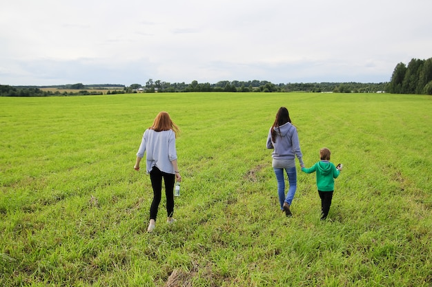 Young beautiful mother walking on the field in summer with her son and daughter
