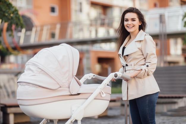 ヨーロッパの市内中心部で乳母車を持って歩いている若い美しい母親。
