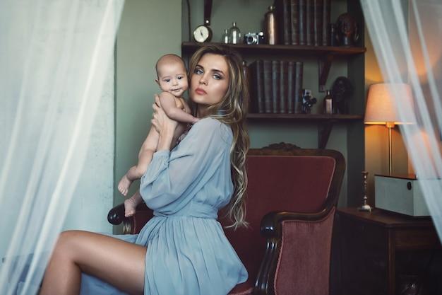 안락의 자에 앉아 그녀의 아기를 손에 들고 고급 회색 드레스를 입고 젊은 아름다운 어머니