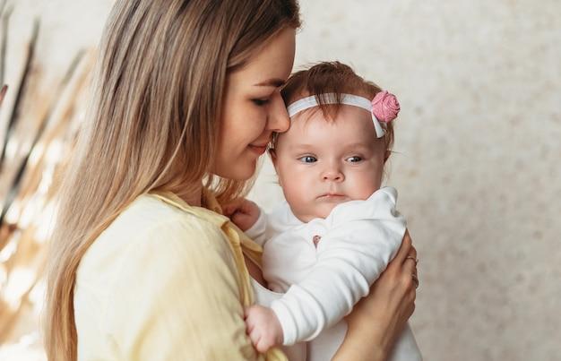 彼女の腕の中で女の子の赤ちゃんを持つ若い美しい母親。優しさと抱擁