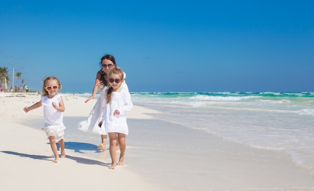 Young beautiful mother with her adorable little daughters running on white beach