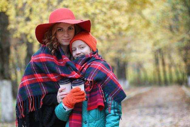 Молодая красивая мать с дочерью на природе. девушка в шляпе гуляет по парку. девушка в осеннем городском парке в листопад.