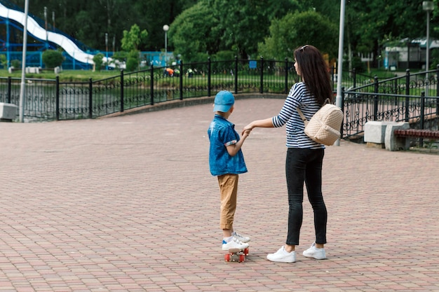 Young beautiful mother with her little cheerful son having fun and skating outdoors
