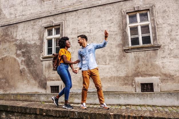 Молодая красивая многокультурная хипстерская пара веселится в старой части города.