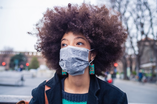 Young beautiful multiethnic woman wearing medical mask protecting from pollution and virus