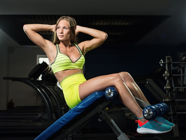 Young beautiful muscular girl trains the press in the gym
