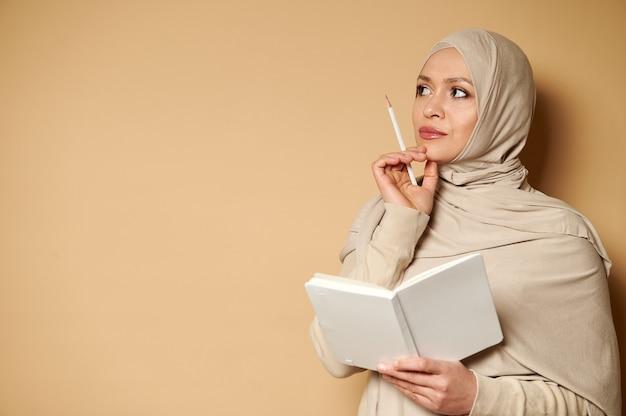 彼女のあごに白いメモ帳と鉛筆を持って物思いにふける表情で横を向いているヒジャーブの若い美しいイスラム教徒の女性
