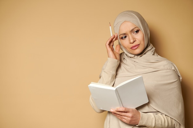 彼女の寺院で白いメモ帳と鉛筆を持って物思いにふける表情で横を向いているヒジャーブの若い美しいイスラム教徒の女性