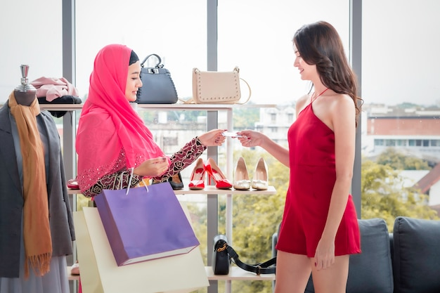 Young beautiful muslim woman sent creadit card to caucasian friendships at clothes shop.