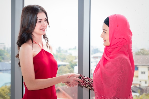 Young beautiful muslim woman shaking hand with caucasian friendships.