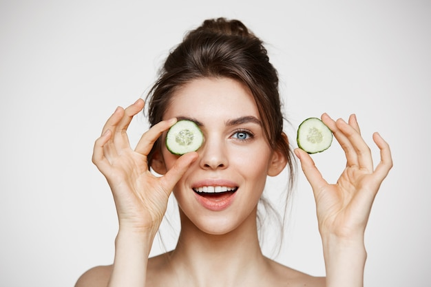 Young beautiful naked girl smiling hiding eye behind cucumber slice looking at camera over white background.