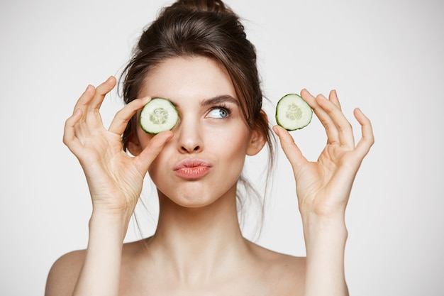 Young beautiful naked girl smiling hiding eye behind cucumber slice over white background. beauty spa and cosmetology concept.