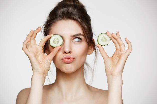 Occhio nascondentesi sorridente della giovane bella ragazza nuda dietro la fetta del cetriolo sopra fondo bianco. concetto di bellezza spa e cosmetologia.