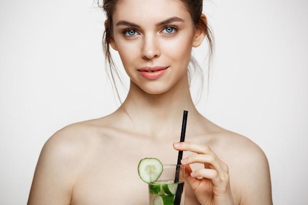 白い背景の上にキュウリのスライスと水のガラスを保持しているカメラを見て笑って完璧なきれいな肌を持つ若い美しい裸の女の子。フェイシャルトリートメント。