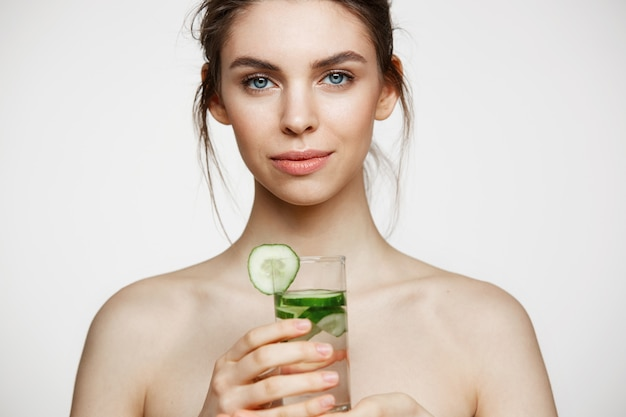 Young beautiful naked girl with perfect clean skin smiling looking at camera holding glass of water with cucumber slices over white background. facial treatment.