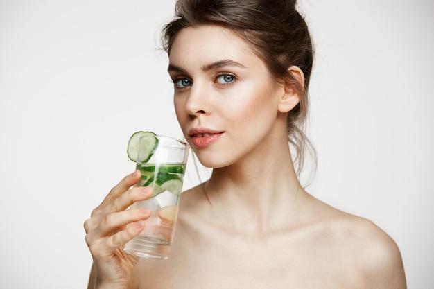 Giovane bella ragazza nuda con pelle pulita perfetta che sorride esaminando macchina fotografica che tiene bicchiere d'acqua con le fette del cetriolo sopra fondo bianco. trattamento facciale.