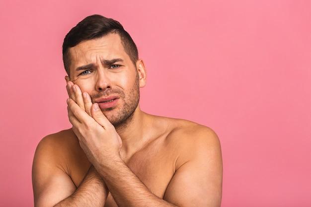歯痛に苦しんでいる浴室の若い美しい裸の男