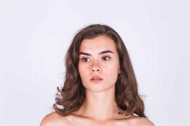 裸の肩を持つ白い壁にそばかすの軽い化粧をした若い美しい自然な柔らかくきれいな肌の女性