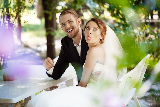 Young beautiful newlyweds fooling, sitting in cafe outdoors.