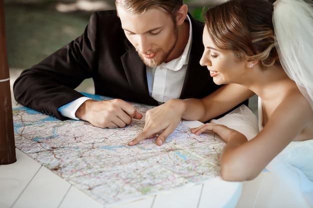 Young beautiful newlyweds smiling, choosing honeymoon trip, looking at map.