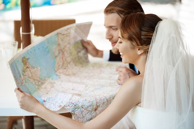 Young beautiful newlyweds smiling, choosing honeymoon trip, looking at map.