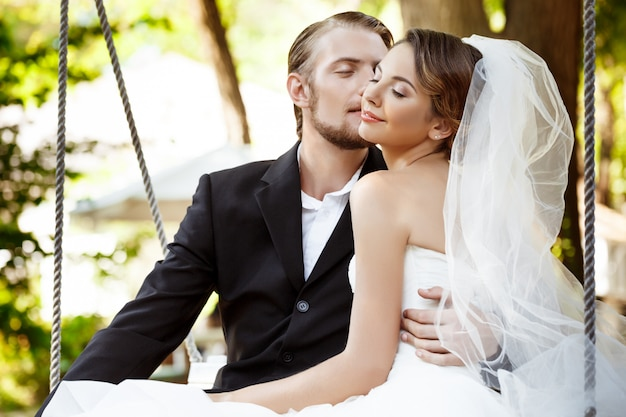 Young beautiful newlyweds smiling, kissing, sitting on swing in park.