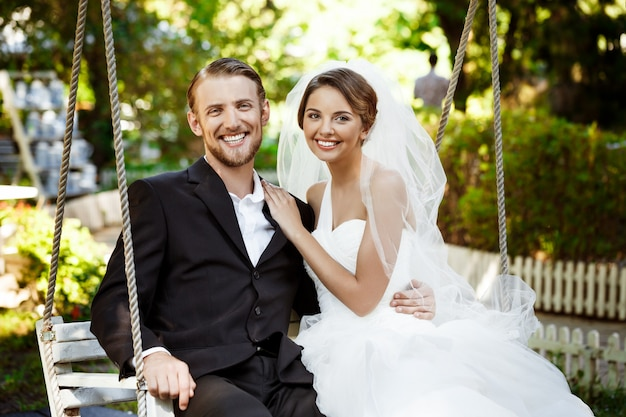 Young beautiful newlyweds smiling, laughing, sitting on swing in park.