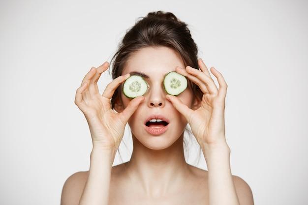 Giovane bella ragazza nuda con gli occhi nascondentesi della bocca aperta dietro le fette del cetriolo sopra fondo bianco. bellezza cura della pelle e cosmetologia.