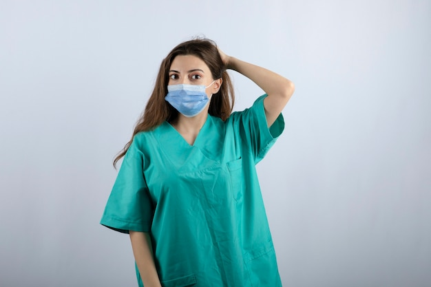 의료 마스크를 쓰고 녹색 제복을 입은 젊은 아름다운 간호사