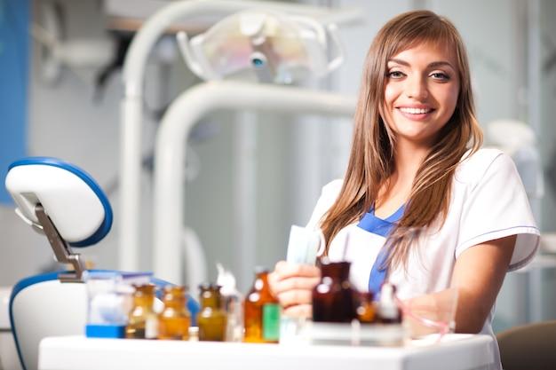 歯科医院の歯科用椅子の近くに座っている白い制服を着た若い美しい看護師の女性