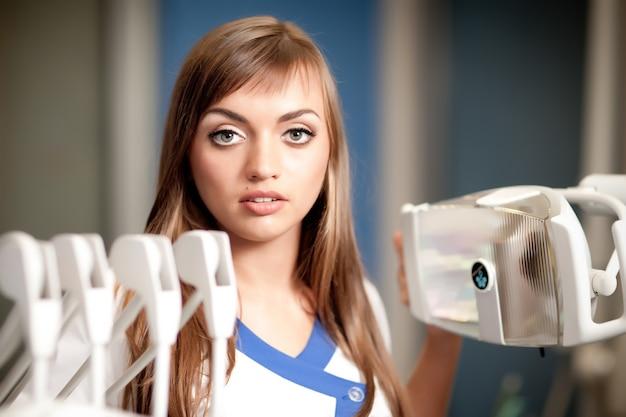 歯科椅子の近くに座っている白い制服を着た若い美しい看護師の女性