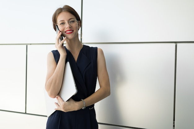 Young beautiful office woman with bright makeup, red lips, glasses sits, communicates with someone