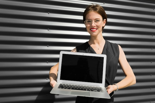 Young beautiful office woman with bright makeup, red lips, glasses stands near the office and show laptop