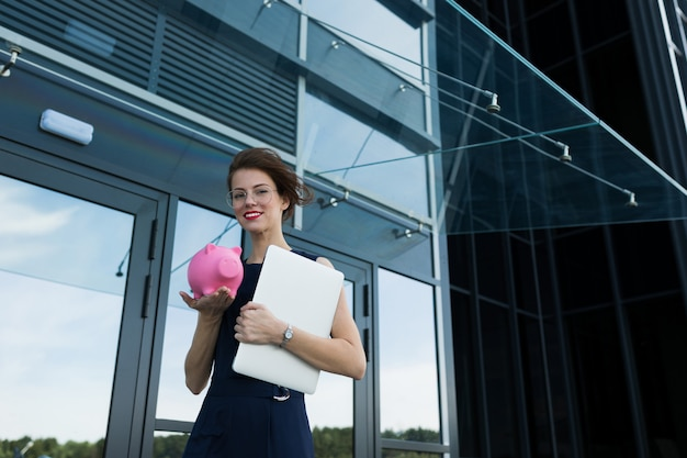 Young beautiful office woman with bright makeup, red lips, glasses stands near the office with papers and shows a pink pig moneybox