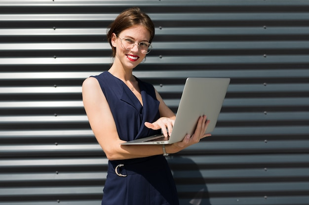 Young beautiful office woman with bright makeup, red lips, glasses stands near the office and work with laptop