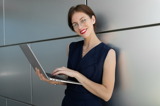 Young beautiful office woman with bright makeup, red lips, glasses works with laptop